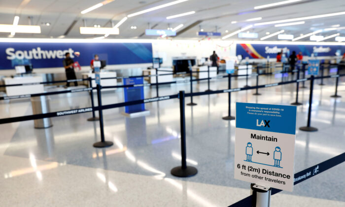 Social distancing sign is displayed at a check-in area for Southwest Airlines Co. at Los Angeles International Airport (LAX) on an unusually empty Memorial Day weekend during the outbreak of the coronavirus disease (COVID-19) in Los Angeles, California, U.S., May 23, 2020. (Reuters/Patrick T. Fallon)