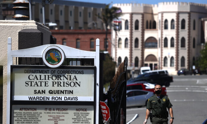 A California Department of Corrections and Rehabilitation (CDCR) officer stands guard at the front gate of San Quentin State Prison in San Quentin, Calif., on June 29, 2020. (Justin Sullivan/Getty Images)