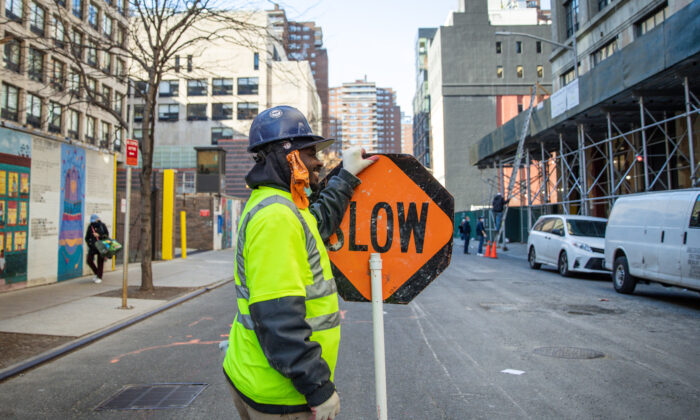 A construction worker holds a traffic sign in Manhattan, New York City, on Nov. 20, 2020. (Samira Bouaou/The Epoch Times)