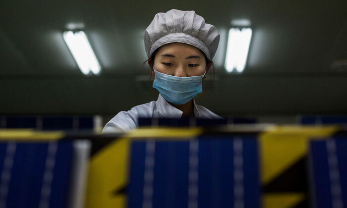 A technician from Yingli Solar prepares solar cells in Hebei Province, China, on Dec. 4, 2014. (Photo by Kevin Frayer/Getty Images)
