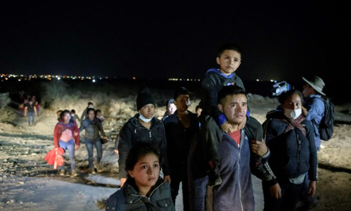 Immigrants who arrived illegally from across the Rio Grande river from Mexico make their way along a track towards a processing checkpoint set up by Border Patrol agents in the border city of Roma, Texas, on March 27, 2021. (Ed Jones/AFP via Getty Images)