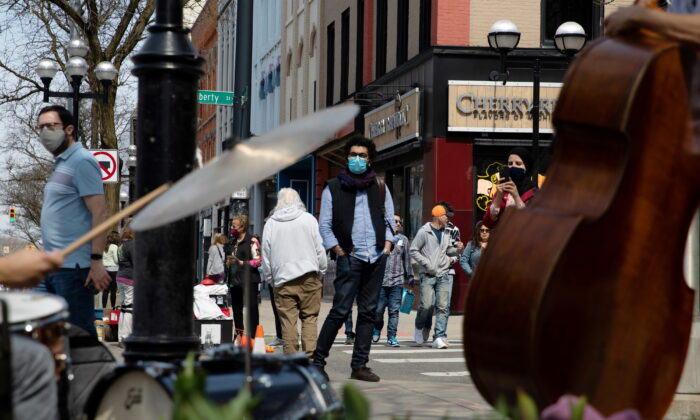A band performs while crowds of people walk as COVID-19 restrictions are eased in Ann Arbor, Mich., on April 4, 2021. (Emily Elconin/Reuters)