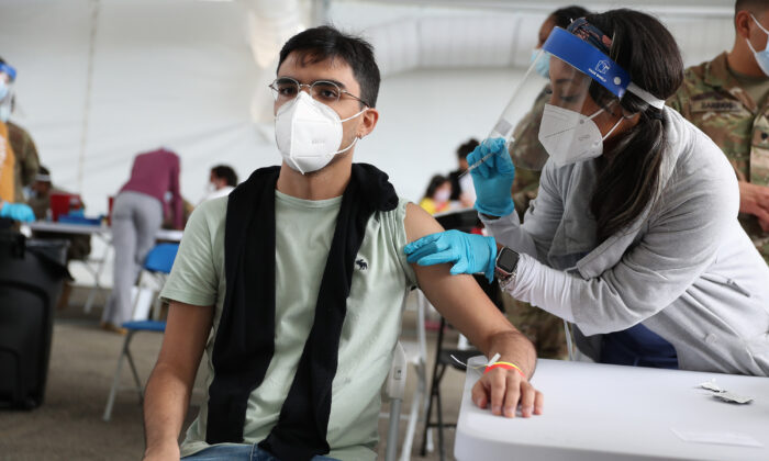 A health care worker immunizes Juan Guevara with the Pfizer COVID-19 vaccine at the Miami Dade College North Campus in North Miami, Fla., on March 10, 2021. (Joe Raedle/Getty Images)