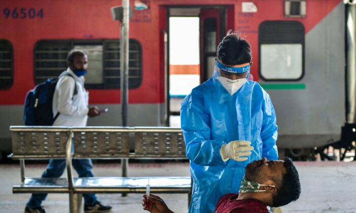 A health worker collects a sample from a passenger for a Reverse Transcription Polymerase Chain Reaction (RT-PCR) test at the Yesvantpur railway station in Bangalore on April 5, 2021. (Manjunath Kiran /AFP via Getty Images)