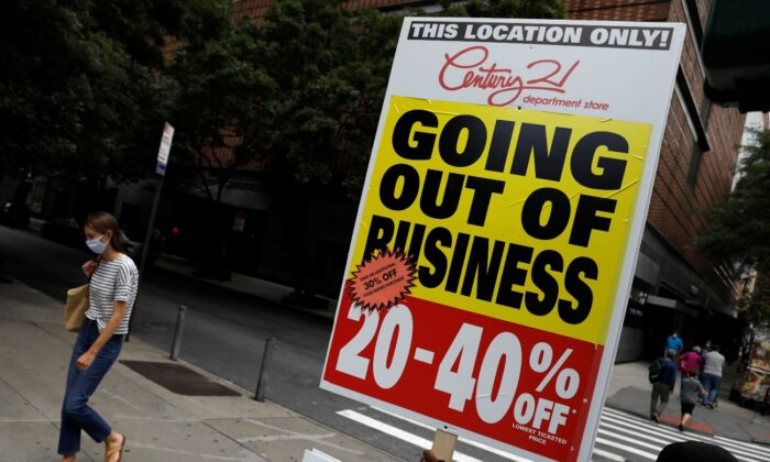 A person holds a sign advertising a sale at Century 21, a retail outlet that announced it was filing for bankruptcy and closing its stores due to the economic impact of the coronavirus disease in Manhattan, New York City, on Sept. 26, 2020. (Andrew Kelly/File/Reuters)
