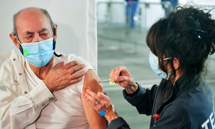 Maximo Michua, 74, holds his sleeve as Kathryne Acuna (R), Director of Ambulatory Clinical Services at Kaiser Permanente, administers his Covid-19 vaccine at a parking structure at Cal Poly Pomona University in Pomona, Calif., on Feb. 5, 2021. (Frederic J. Brown/AFP via Getty Images)