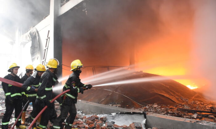 Burma Fire Services Department staff puts out the flames at JOC Galaxy (Myanmar) Apparel Co. in Hlaing Thar Yar township, Yangon, Burma, on April 7, 2021. (Fire Services Department/Handout via Reuters)
