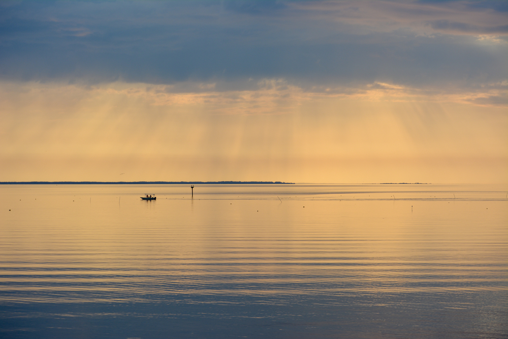 Sunrise,Over,The,Chesapeake,Bay,With,A,Boat,Working,The