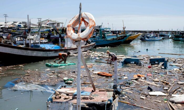 Indonesian men look for salvageable items amid debris and damaged boats following a storm at a port in Kupang, East Nusa Tenggara province, Indonesia, on April 7, 2021. (Armin Septiexan/AP Photo)