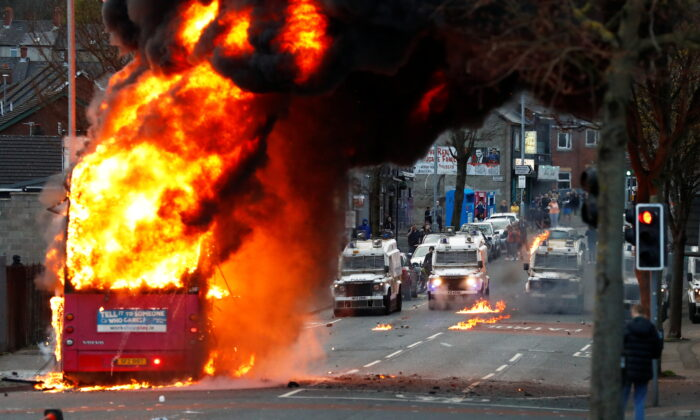 Police vehicles are seen as a hijacked bus burns on the Shankill Road as protests continue in Belfast, Northern Ireland, on April 7, 2021. (Jason Cairnduff/Reuters)