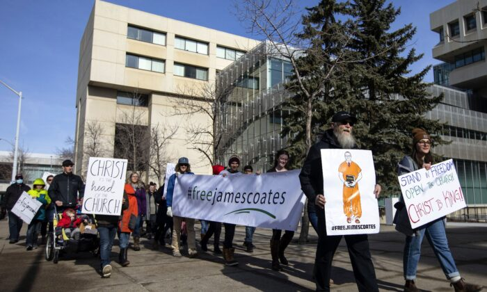 In a file photo from March 4, 20121, supporters rally outside court as Pastor James Coates of GraceLife Church appeals his bail conditions after he was arrested for holding church services in violation of COVID-19 rules, in Edmonton. (The Canadian Press/Jason Franson)