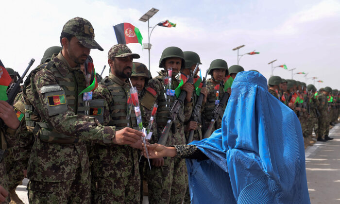 An Afghan woman wearing a burqa gives roses to Afghan National Army (ANA) soldiers during a ceremony in a military base in the Guzara district of Herat Province on Feb. 28, 2019. (Hoshang Hashimi/AFP via Getty Images)