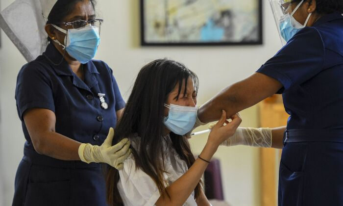 A health worker inoculates the Chinese-made Sinopharm vaccine to a Chinese national living in Sri Lanka, at the Colombo Port City project premises, in Colombo, Sri Lanka on April 6, 2021. (Ishara S. Kodikara/AFP via Getty Images)