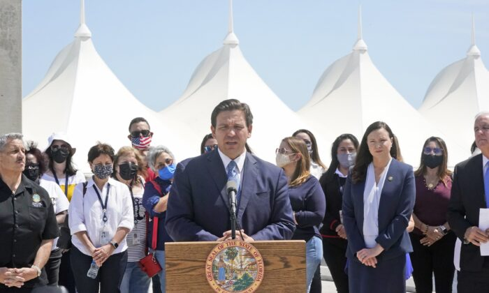 Florida Gov. Ron DeSantis, center, surrounded by officials and cruise workers, speaks during a news conference to announce a lawsuit against the federal government, at Port Miami in Miami, Fla., on April 8, 2021. (Wilfredo Lee/AP Photo)
