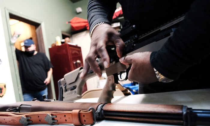 Lateif Dickerson handles some of his rifles at his gun instruction headquarters in Jersey City, N.J., on March 25, 2021. (Spencer Platt/Getty Images)