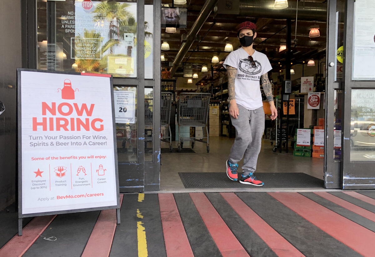 A customer walks by a now hiring sign