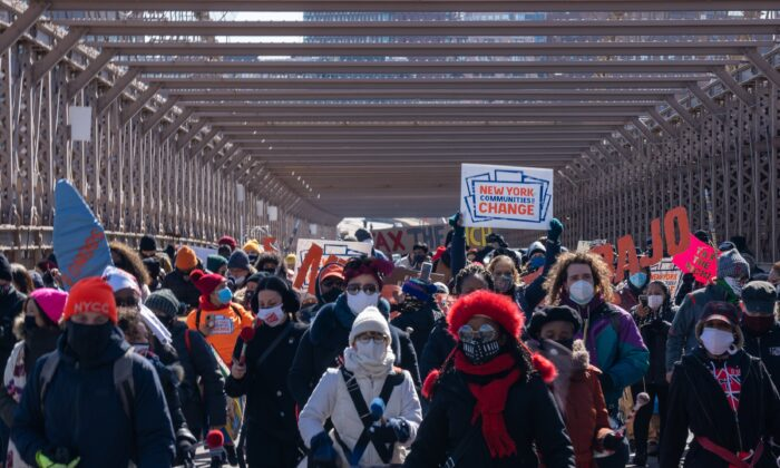 Protestors march across the Brooklyn Bridge to demand funding for excluded workers in the New York State budget, in New York City on March 5, 2021. (David Dee Delgado/Getty Images)