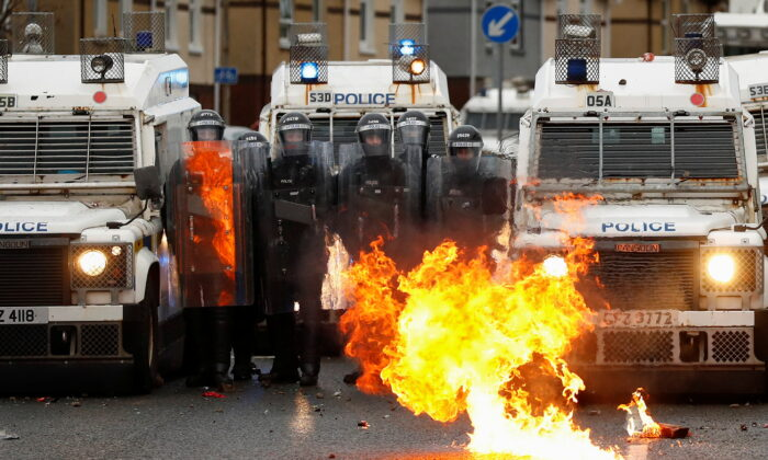 A fire burns in front of the police on the Springfield Road as protests continue in Belfast, Northern Ireland, on April 8, 2021. (Jason Cairnduff/Reuters)