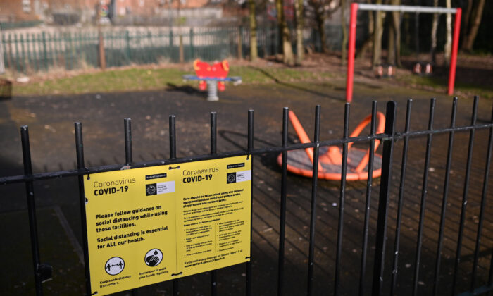 A COVID-19 information poster is pictured on the fence of an empty children's play park in Manchester, northern England, on Feb. 15, 2021. (Oli Scarff/AFP via Getty Images)