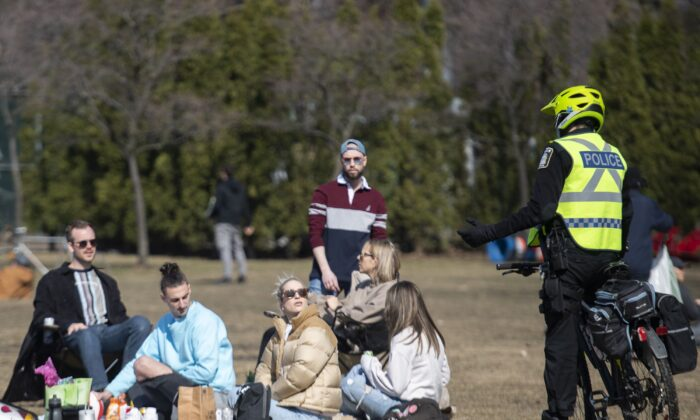 Police talk with people as they gather in a park in Montreal on April 4, 2021. (The Canadian Press/Graham Hughes)