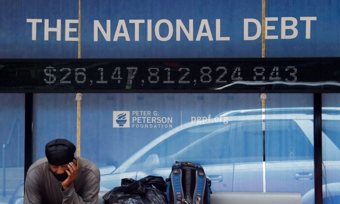 A man waits at a bus stop that displays the national debt of the United States in Washington, D.C., on June 19, 2020. (Olivier Douliery/AFP via Getty Images)