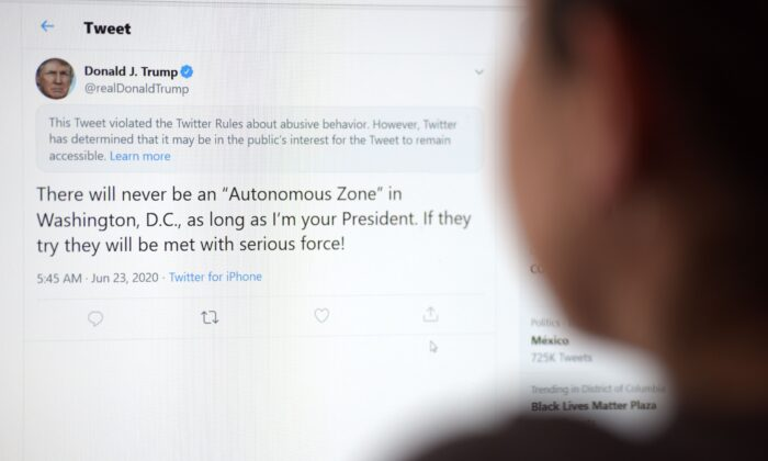 This illustration photo shows a woman in Los Angeles looking at the official Twitter account of then-President Donald Trump on June 23, 2020. (AFP via Getty Images)