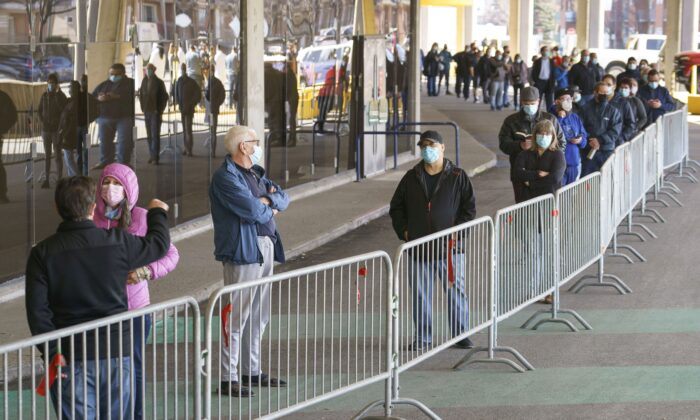 People wait in line at a COVID-19 vaccination clinic at Olympic Stadium in Montreal on April 8, 2021. (The Canadian Press/Paul Chiasson)