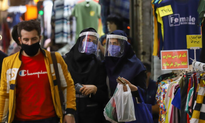 Iranian women wear protective face shields and masks as they walk in Tehran Bazaar in Tehran,Iran, onApril 6, 2021. (Majid Asgaripour/West Asia News Agency via Reuters)