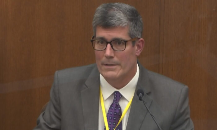 In this image from video, Dr. Andrew Baker, Hennepin County Medical Examiner, testifies as Hennepin County Judge Peter Cahill presides in the trial of former Minneapolis police Officer Derek Chauvin at the Hennepin County Courthouse in Minneapolis, on April 9, 2021. (Court TV via AP/Pool)