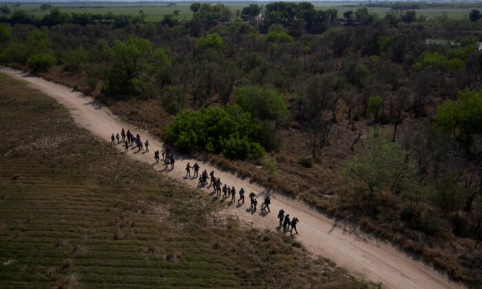 Families from Central America walk toward the border wall after crossing the Rio Grande river into the United States from Mexico on rafts in Penitas, Texas, on March 26, 2021. (Adrees Latif/Reuters)