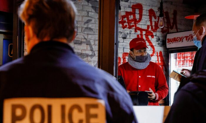 French police officers inspect a restaurant during a nationwide curfew, from 6 p.m to 6 a.m, due to tighter measures against the spread of the CCP virus disease (COVID-19), in Paris on Feb. 5, 2021. (Sarah Meyssonnier/Reuters)