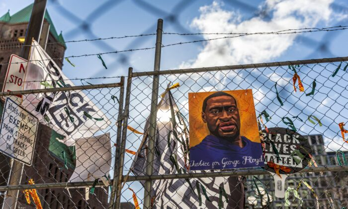 """A poster with George Floyd's picture and a sign reads that """"I Can't Breathe"""" hang from a security fence outside the Hennepin County Government Center in Minneapolis, on March 31, 2021. (Kerem Yucel/AFP via Getty Images)"""