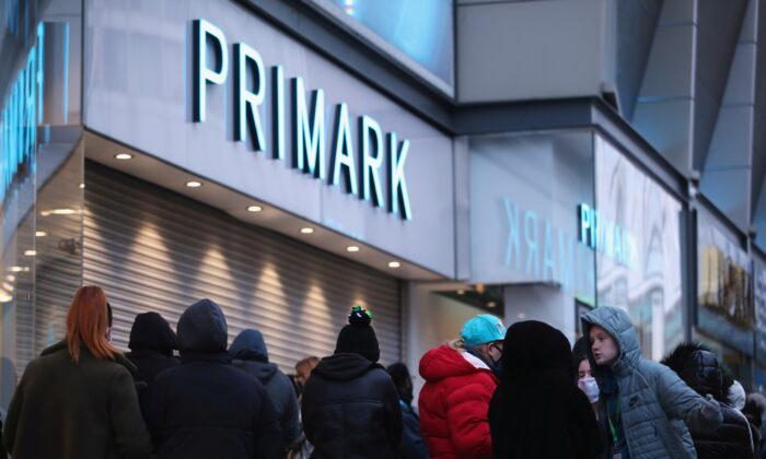 Klanten staan in de rij om naar binnen te gaan, aangezien de winkel Primark in Birmingham, Groot-Brittannië, zijn deuren heropent na een derde lockdown begin januari vanwege de aanhoudende COVID-19-pandemie op 12 april 2021. (Carl Recine / Reuters)
