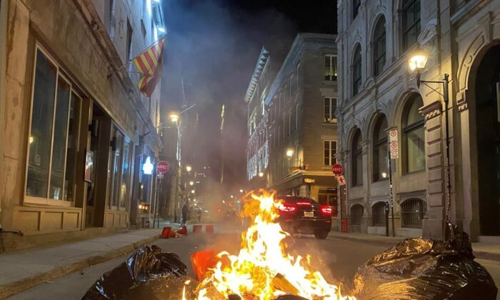 Garbage fires were lit as hundreds of people gathered on Sunday evening in the streets of Old Montreal to protest against the return of the 8 p.m. curfew in the city. (The Canadian Press)