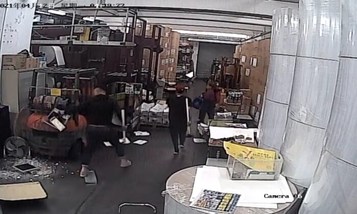 Two intruders dressed in black holding hammers caught on CCTV at the print shop that prints the Hong Kong edition of The Epoch Times on April 12, 2021. (The Epoch Times)