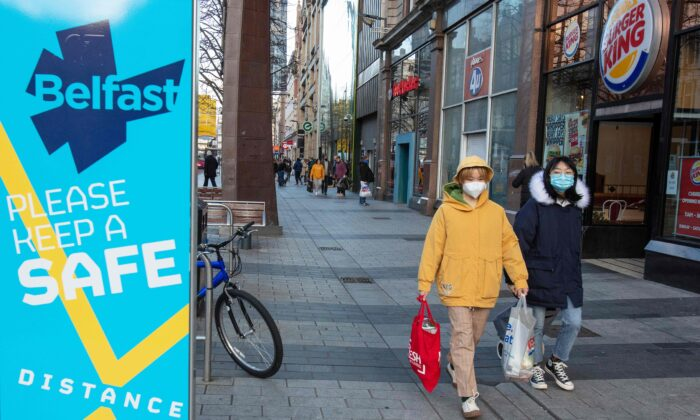 Shoppers wearing protective face coverings to combat the spread of the CCP virus, walk through Belfast city centre, in Northern Ireland, UK, on Dec. 24, 2020. (Paul Faith /AFP via Getty Images)
