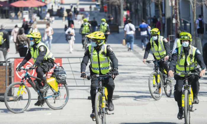 Police officers patrol Sainte-Catherine Street in Montreal on April 10, 2021. (Graham Hughes/The Canadian Press)
