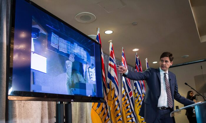 B.C. Attorney General David Eby gestures toward a screen showing bundles of cash an individual brought to a casino, after releasing an independent review of anti-money laundering practices during a news conference in Vancouver on June 27, 2018. (The Canadian Press/Darryl Dyck)