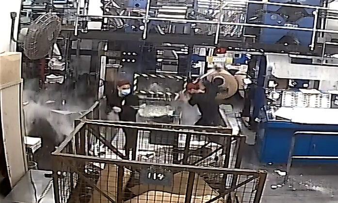 A CCTV screenshot showing intruders dressed in black, one wielding a sledge-hammer, damaging printing press equipment at the print shop of the Hong Kong edition of The Epoch Times on April 12, 2021.(The Epoch Times)