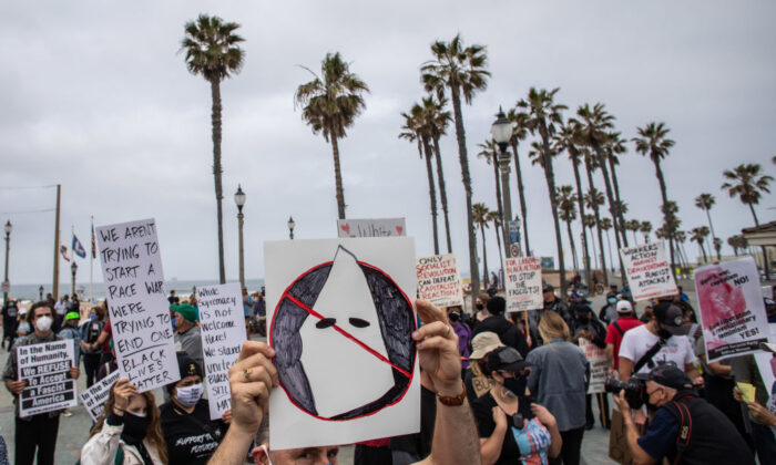 A man holds an anti-KKK sign during a protest against white supremacy in Huntington Beach, Calif., on April 11, 2021. (Apu Gomes/Getty Images)