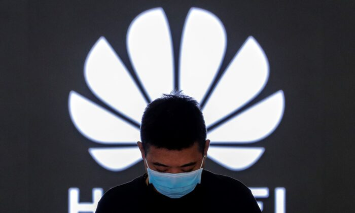 An employee stands inside a Huawei flagship store in Beijing, on April 12, 2021. (Andy Wong/AP Photo)