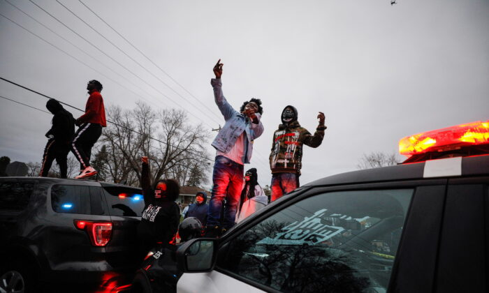 Demonstrators stand on a police vehicle during a protest after police shot and killed a man, Daunte Wright, in Brooklyn Center, Minnesota, on April 11, 2021. (Nick Pfosi/Reuters)