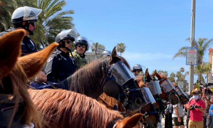 Police monitor a gathering of Black Lives Matter supporters in Huntington Beach, Calif., on April 11, 2021. (Tomas Morales)