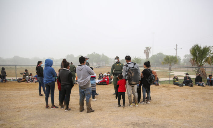 A group of illegal immigrants with Border Patrol after crossing the U.S.-Mexico border in La Joya, Texas, on April 10, 2021. (Charlotte Cuthbertson/The Epoch Times)