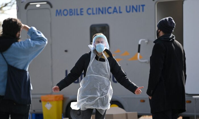 A worker dressed in PPE talks with members of the public arriving to take COVID-19 tests at a mobile novel coronavirus surge testing centre in Brockwell Park in south London, on Apr. 13, 2021. (Daniel Leal-Olivas/AFP via Getty Images)