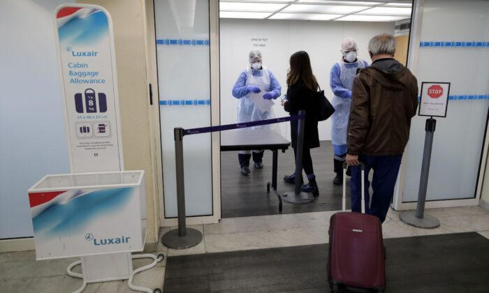 Medical workers prepare to test passengers as they arrive at Nice Cote d'Azur Airport in Nice, France, on March 1, 2021. (Eric Gaillard/Reuters)