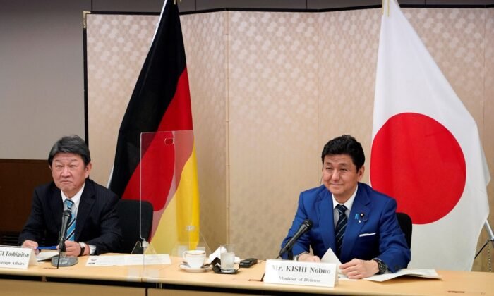 Japan's Foreign Minister Toshimitsu Motegi (L) and Defence Minister Nobuo Kishi (R) attend a video conference with German Foreign Minister Heiko Maas (not pictured) and Defence Minister Annegret Kramp-Karrenbauer (not pictured) at the Foreign Ministry in Tokyo, Japan, on April 13, 2021. (Franck Robichon/Pool via Reuters)