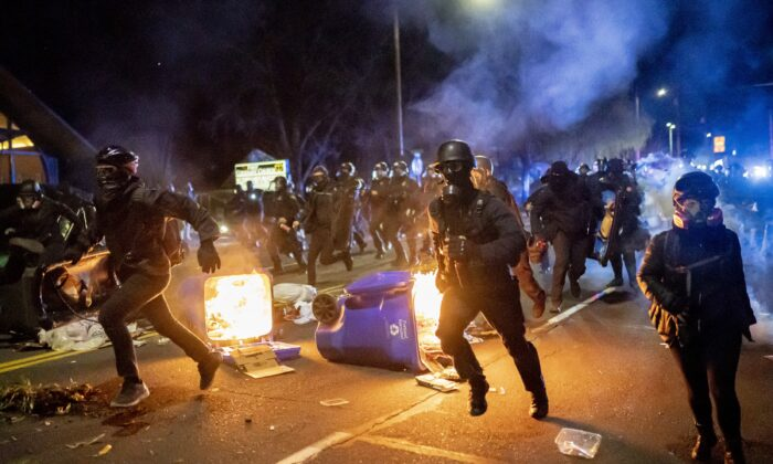 Portland police officers chase demonstrators after a riot was declared during civil unrest over the shooting in Minnesota of Daunte Wright, in Portland, Ore., on April 12, 2021. (Nathan Howard/Getty Images)