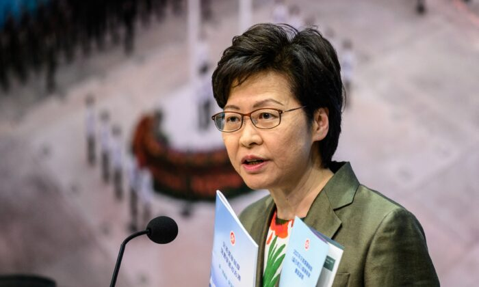 "Hong Kong Chief Executive Carrie Lam holds a pamphlet for the ""Improving Electoral System (Consolidated Amendments) Bill 2021"" as she speaks during a press conference at the government headquarters in Hong Kong on April 13, 2021. (Anthony Wallace/AFP via Getty Images)"