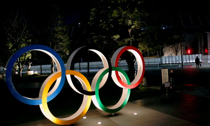 The Olympic rings are illuminated in front of the National Stadium in Tokyo, Japan on Jan. 22, 2021. (Kim Kyung-Hoon/Reuters)